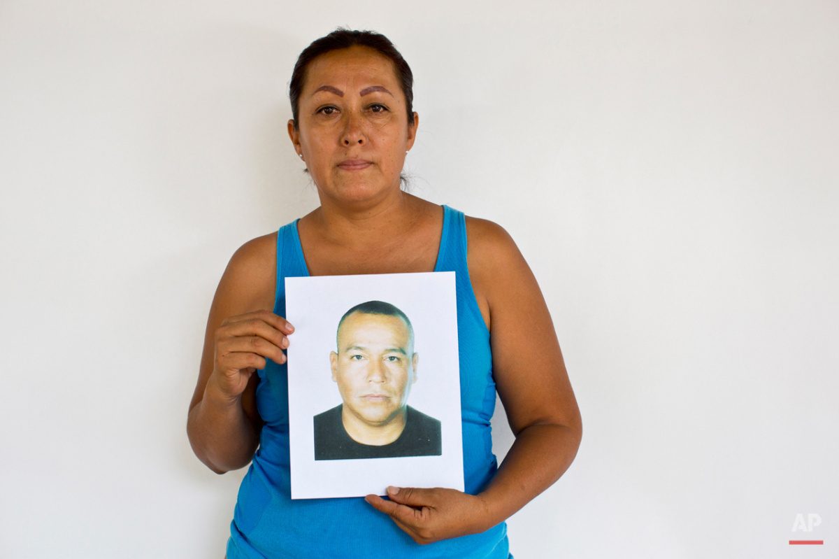 In this May 13, 2015 photo, Maria del Carmen Abarca holds up a photo of her husband, Saturno Giles Beltran, in Iguala, Mexico. Abarca's husband was an Iguala police officer in the departmentís stolen vehicles unit. It quickly became apparent to the retired soldier that he was the only clean officer in his unit. He warned his wife and daughters to avoid certain parts of Iguala where police took women, and told them never to come to the police station. He was taking classes for a law degree on weekends, promising his wife, that he would leave the police force as soon as he earned his degree. He disappeared on March 8, 2014, driving to class. He called the next day and without specifying who, said they had allowed him a phone call. He said he was clearing up some questions so he could come home. That was the last his wife heard from him. She fears word got out in the police department that he was going to leave and someone decided not to let him. (AP Photo/Dario Lopez-Mills)