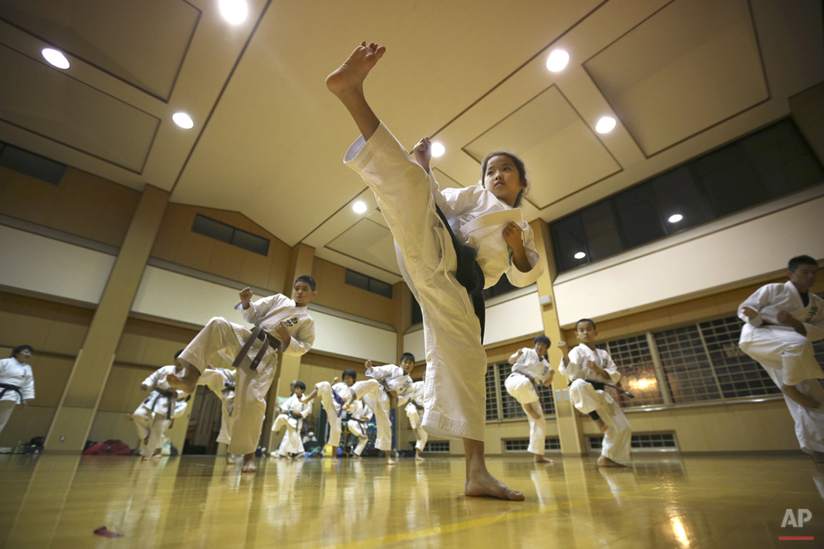 "In this Nov. 18, 2015 photo, 9-year-old Mahiro Takano, center, three-time Japan karate champion in her age group practices in Nagaoka, Niigata Prefecture, north of Tokyo.  Mahiro stars in singer Sia's latest music video ""Alive,"" the just-released single from the singer's upcoming album. Her kicks, turns and punches in the air are part of ""kata"" forms that are like choreography in the Japanese defensive martial art of karate. Kata competition is separate from combat matches, which are also part of the sport. (AP Photo/Eugene Hoshiko)"