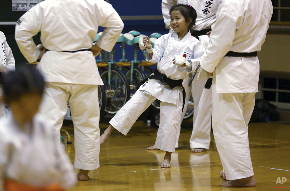 "In this Nov. 18, 2015 photo, 9-year-old Mahiro Takano, center, three-time Japan karate champion in her age group chat with her karate instructors during practice in Nagaoka, Niigata Prefecture, north of Tokyo. Mahiro stars in singer Sia's latest music video ""Alive,"" the just-released single from the singer's upcoming album. (AP Photo/Eugene Hoshiko)"