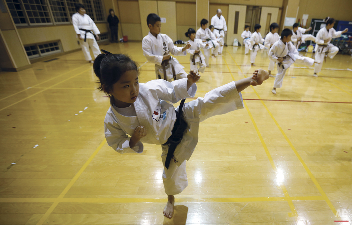 "In this Nov. 18, 2015 photo, 9-year-old Mahiro Takano, center, three-time Japan karate champion in her age group practices in Nagaoka, Niigata Prefecture, north of Tokyo.  Mahiro stars in singer Sia's latest music video ""Alive,"" the just-released single from the singer's upcoming album. Her kicks, turns and punches in the air are part of ""kata"" forms that are like choreography in the Japanese defensive martial art of karate. Kata competition is separate from combat matches, which are also part of the sport. (AP Photo/ Eugene Hoshiko)"