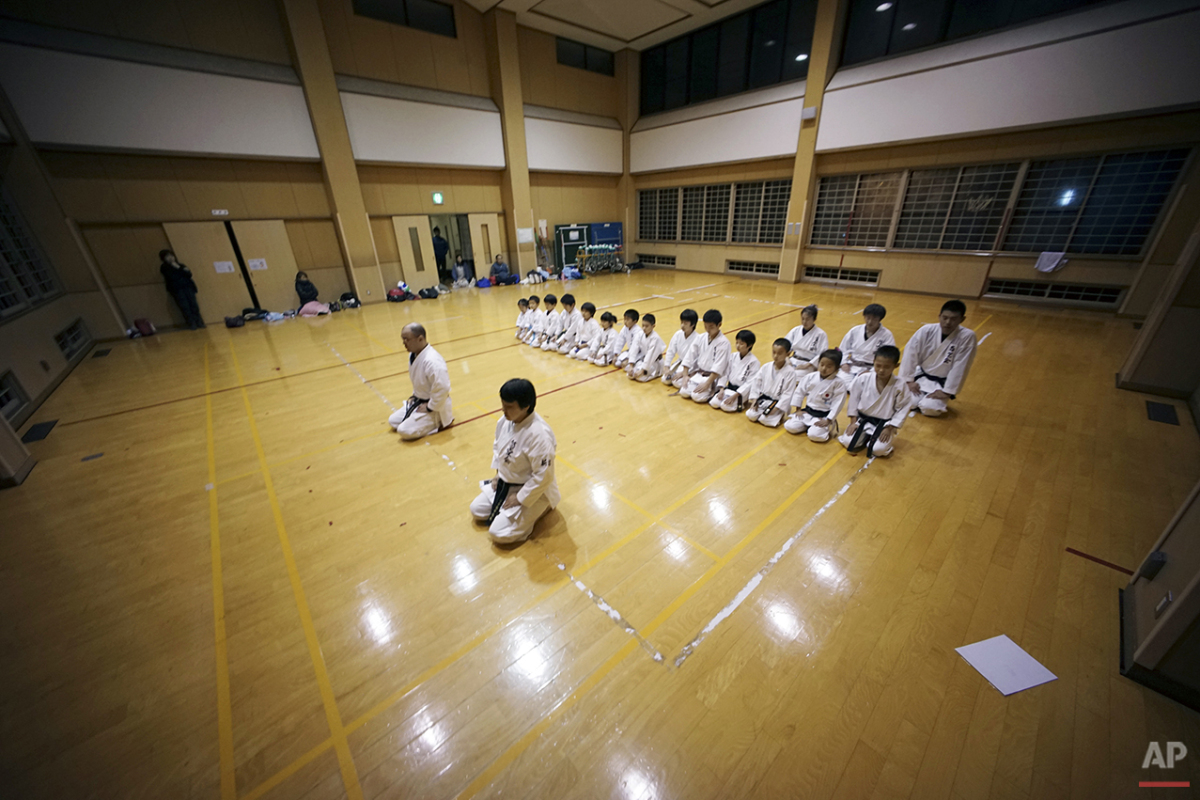"In this Nov. 18, 2015 photo, 9-year-old Mahiro Takano, second from right in middle row, three-time Japan karate champion in her age group sits straight with other fellow karate students at the end of day's practice session in Nagaoka, Niigata Prefecture, north of Tokyo. Mahiro stars in singer Sia's latest music video ""Alive,"" the just-released single from the singer's upcoming album. (AP Photo/ Eugene Hoshiko)"