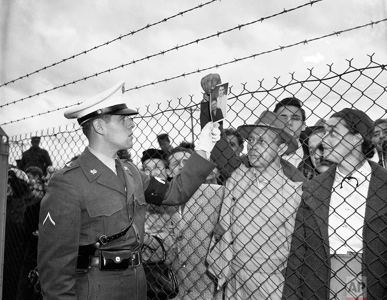 In this Nov. 21, 1951 photo, Bill Vetesy of Colonia, N.J., holds a picture of his mother and brother as he asks a military police officer inside the fence at Camp Kilmer, N.J., if they are among the 60 Hungarian refugees who arrived at the camp. The first plane load of refugees arrived at nearby McGuire Air Force Base from Vienna earlier in the day. The refugees will be housed at Camp Kilmer until quarters in private homes are made available to them in the United States. (AP Photo/Anthoy Camerano)