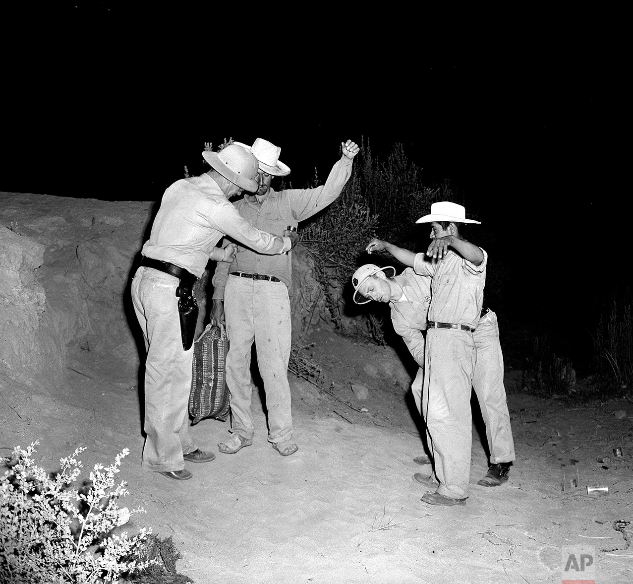 In this Aug. 11, 1951 photo, U.S. Border Patrol inspectors Fred H. Voight, left, and Gordon MacDonald, right, both from the El Centro U.S. Border Patrol sector headquarters, search two Mexican nationals, Pedro Vidal, with bag, and Canuto Garcia, right, shortly after the two men illegally crossed the border from Mexico, west of Calexico, Calif. Mexican laborers try to cross in this area to the United States, to work on the farms of the nearby Imperial Valley. (AP Photo)