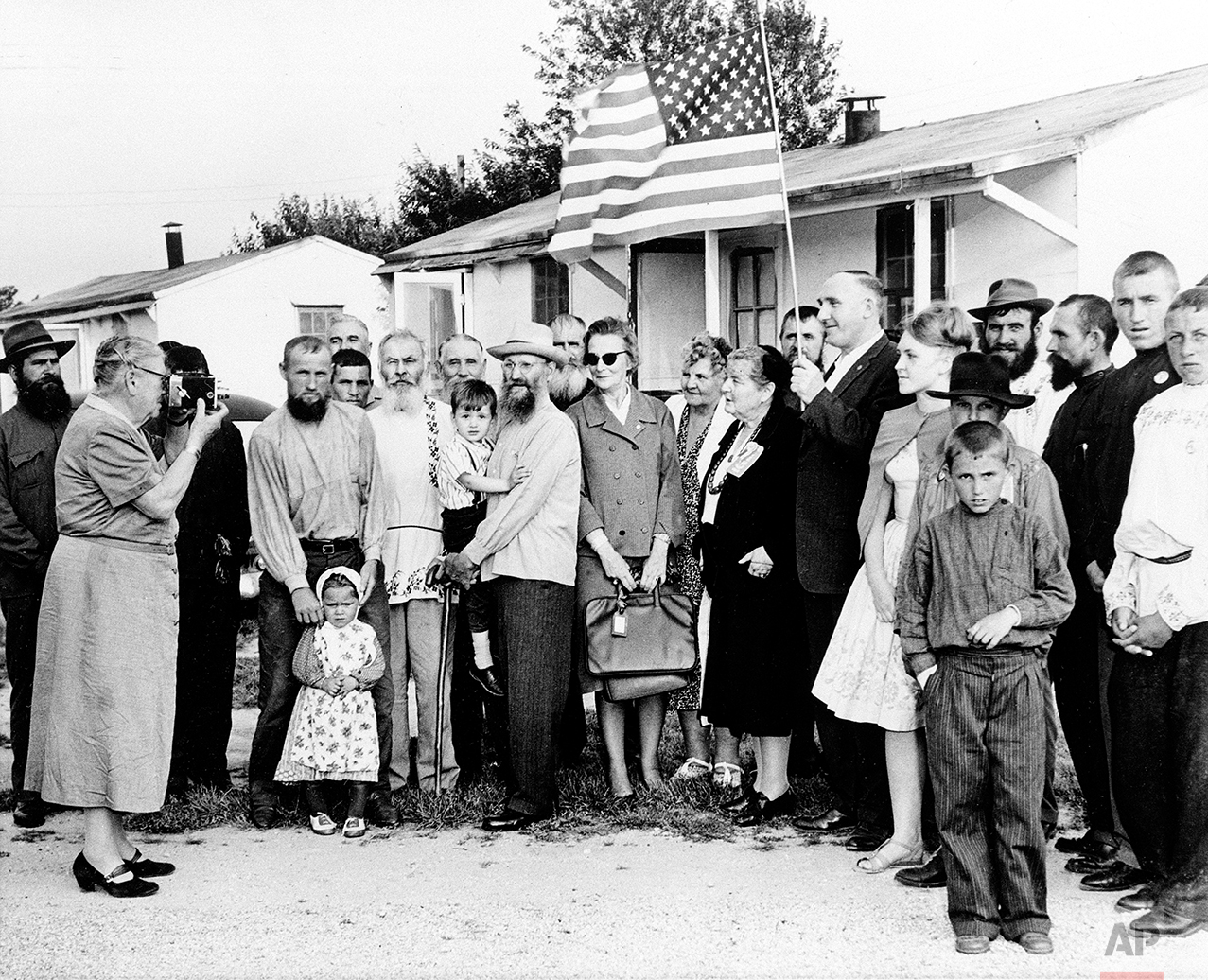 A group of 208 Russians, who arrived at a farm from Ankara, Turkey, pose for a picture taken by Countess Alexandra L. Tolstoy, left, president of the Tolstoy Foundation that sponsored their resettlement in Bridgeton, N.J., June 6, 1963. (AP Photo)