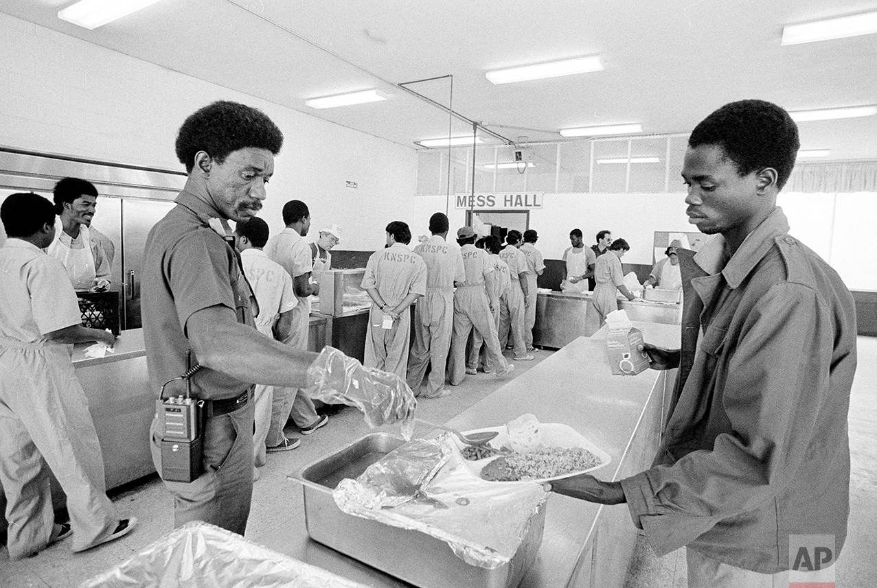 """An inmate at the Krome North Service Processing Center is served lunch by a prison employee, March 4, 1985. The prison, located west of Miami, has been called the """"Caribbean Ellis Island."""" it houses 523 people who were apprehended trying to enter the United States illegally. (AP Photo/Raul de Molina)"""