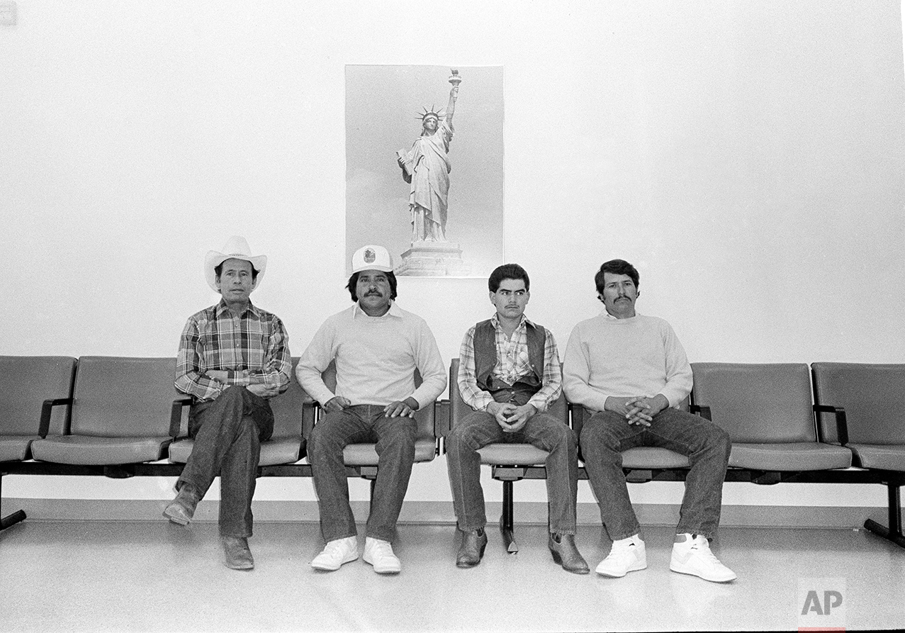 Alejandro Fierro, right, and three other Mexican farm workers sit under a poster of the Statue of Liberty at the U.S. Immigration and Naturalization Service office in Denver, Colo., Nov. 11, 1987. Fierro and the others were waiting to begin the application process for amnesty under the landmark Immigration Control and Reform Act of 1986. From left are: Jose Duenas-Lopez; Jose Santillano; Carlo Castro-Gutierres and Fierro. (AP Photo)