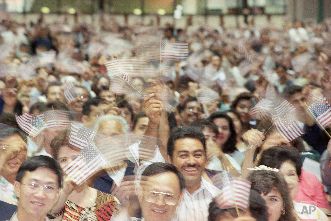 New U.S. citizens wave their flags with excitement during a naturalization ceremony, Wednesday, August 14, 1996 in Los Angeles. Thirty thousand people were naturalized over the past three days in Los Angeles and immigration officials expect 320,000 candidates to becomes U.S. citizens this year in Los Angeles. (AP Photo/Frank Wiese)