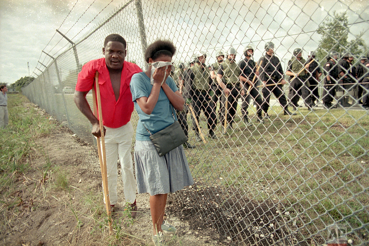 Paula Vivaldy cries as she and friend Bilatois Thermidor walk beside the barbed wire fence at the U.S. Immigration Service's Krome Avenue Detention Center, in Miami,where some 200 Haitians gathered to protest the treatment of Haitians held there, Jan. 29, 1989. Inside the fence several dozen federal officers in riot gear stand at the ready for any trouble. (AP Photo/Kathy Willens)