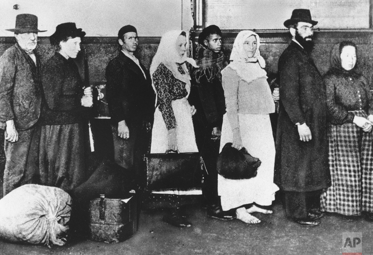 This is an undated photo of a group of immigrants arriving at Ellis Island in New York. They are waiting in line to begin immigration proceedings. (AP Photo)