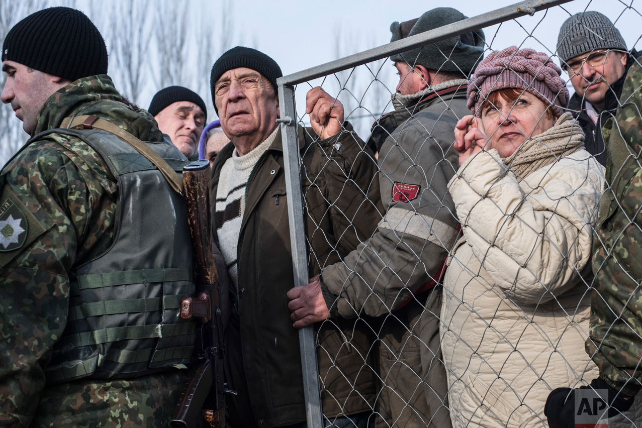 Local residents line up for help at the humanitarian aid center in Avdiivka, eastern Ukraine, Friday, Feb. 3, 2017. Strong shelling hit both government- and rebel-controlled areas of eastern Ukraine in a continued escalation of the country's fighting. (AP Photo/Evgeniy Maloletka)
