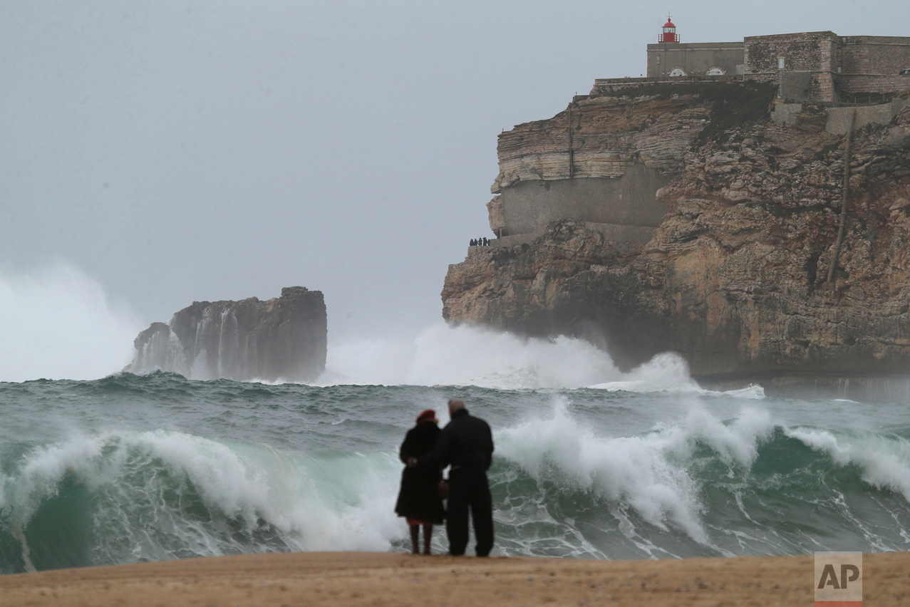 A couple watches the waves break on the coastline in Nazare, Portugal, Thursday, Feb. 2, 2017, as strong winds hit the area. (AP Photo/Armando Franca)