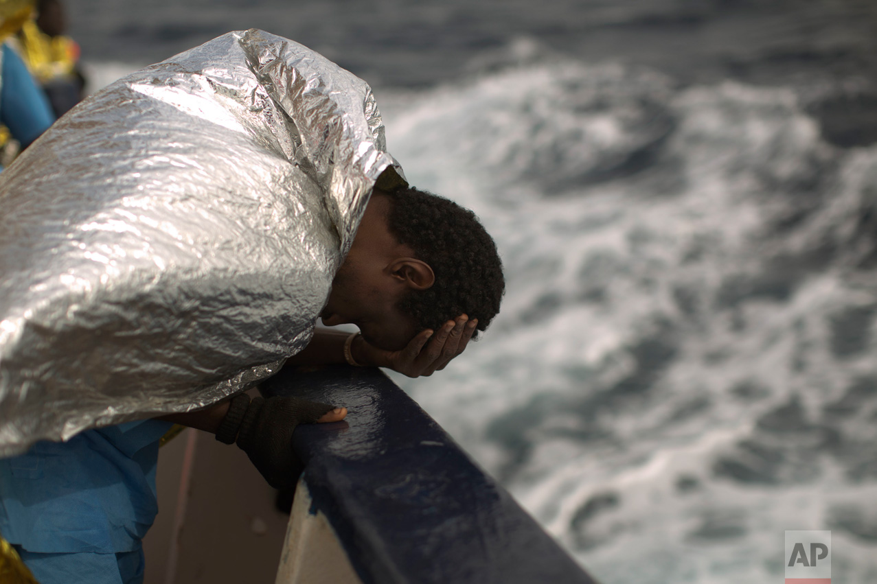 A sub-Saharan migrant holds his head, on the deck of the Golfo Azzurro boat after he was rescued from a rubber boat by members of Proactive Open Arms NGO, on the Mediterranean sea, about 24 miles north of Sabratha, Libya, Saturday, Jan. 28, 2017. (AP Photo/Emilio Morenatti)