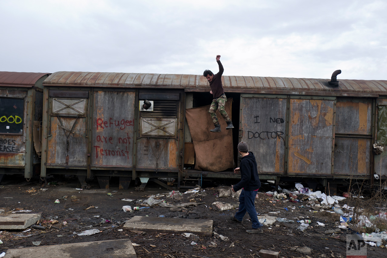 An Afghan refugee jumps off an old train carriage where he and others took refuge in Belgrade, Serbia, Friday, Feb. 3, 2017. Hundreds of migrants have been sleeping amid in freezing temperatures in central Belgrade looking for ways to cross the heavily-guarded EU borders. (AP Photo/Muhammed Muheisen)