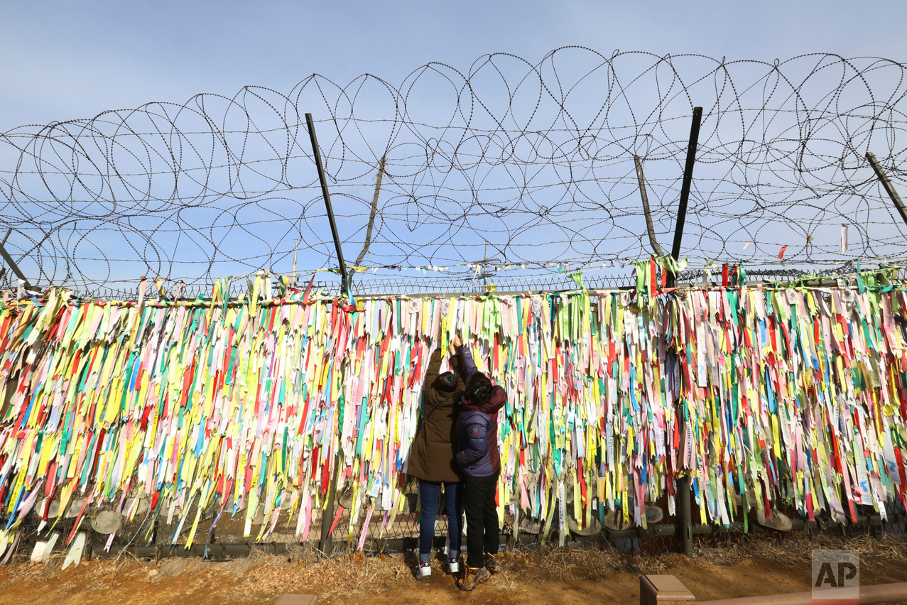 Women hang a ribbon wishing for the reunification of the two Koreas on a fence as they celebrate the Lunar New Year at the Imjingak Pavilion, near the demilitarized zone of Panmunjom, in Paju, South Korea, Saturday, Jan. 28, 2017. Millions of South Koreans visit their hometowns during the four-day holiday. (AP Photo/Ahn Young-joon)