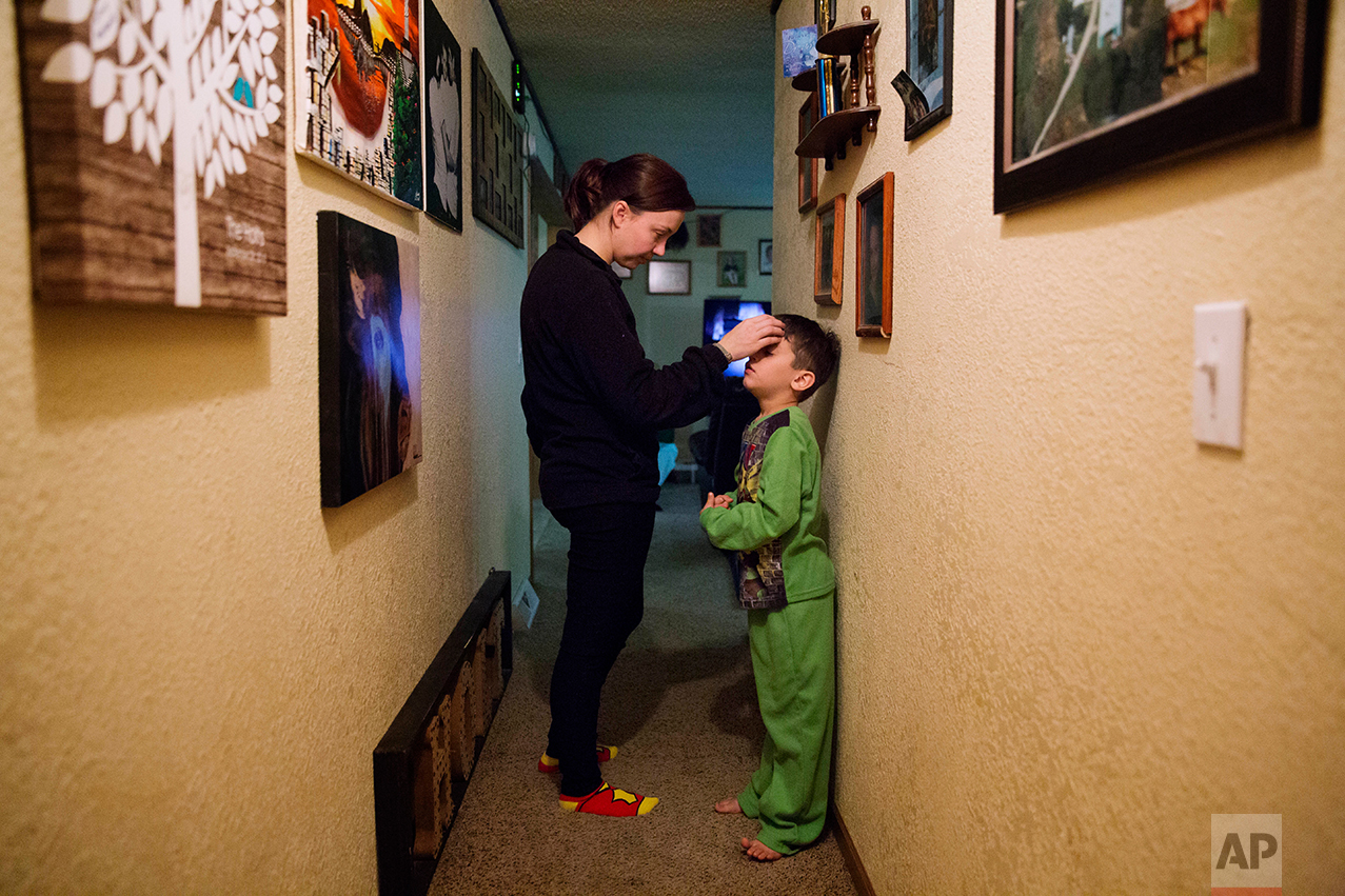 Lydia Holt, left, talks her stepson, Carter, 7, into going to bed at their home in Wauzeka, Wis., Tuesday, Jan. 17, 2017. Holt, who makes $400 a week as an assistant at a law firm and whose husband doesn't do much better at a car parts store, worry that by the time their sons grow up there will be nothing left for them here. (AP Photo/David Goldman)