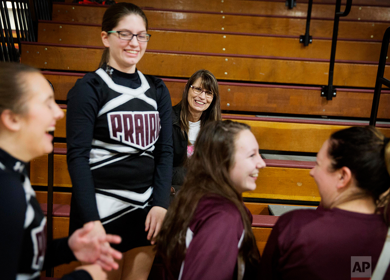 """Marlene Kramer, center, attends a wrestling meet to watch her stepdaughter Sierra, 16, center left, cheerlead at a high school wrestling meet in Prairie du Chien, Wis., Thursday, Jan. 19, 2017. Kramer thinks Barack Obama inherited a country in trouble, and he did as good a job as he could in the time that he had. She admires him, still. But she voted for Donald Trump. """"His things aren't going the way we want them here,"""" she said, """"so we needed to go in another direction."""" (AP Photo/David Goldman)"""