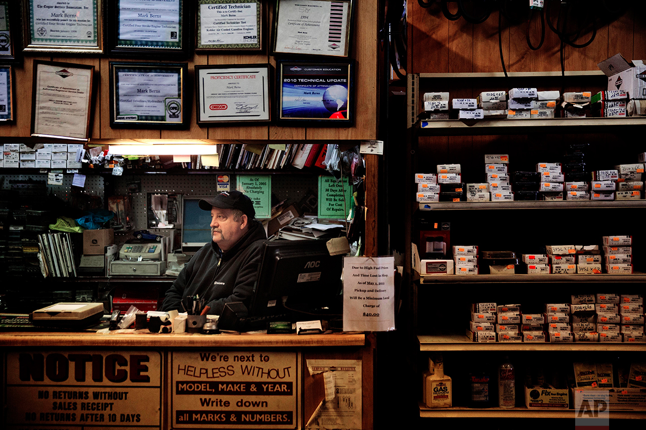 """Mark Berns sits in his small engine repair shop in Prairie du Chien, Wis., Thursday, Jan. 19, 2017. """"If you ask anybody here, we'll all tell you the same thing: We're tired of living like this. We've been railroaded, run over by the politicians and run over by laws,"""" said Berns in the shop he can barely afford to keep open anymore. He drives a 14-year-old truck with 207,000 miles on it because he doesn't make enough profit to buy a new one. Berns watched Trump's first days in office half-hopeful, half-frightened about the future but said he's willing to give him the benefit of the doubt. (AP Photo/David Goldman)"""