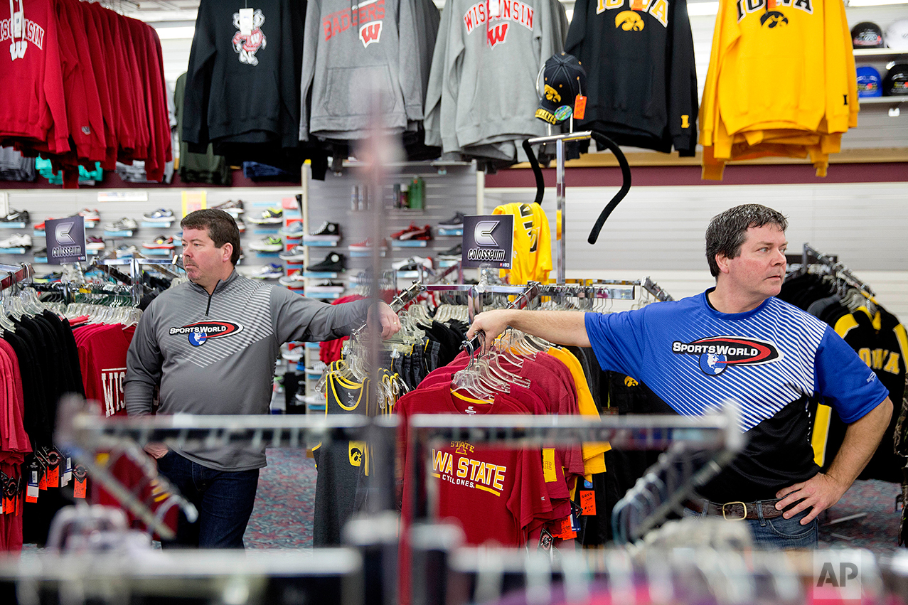 Brothers Todd, right, and Scott Yeomans, owners of a custom sportswear company, stand in their store in Prairie du Chien, Wis., Friday, Jan. 20, 2017. They said they're trying to do the right thing by making their products with American-made fabrics and American labor, but they're competing against companies that use factories overseas. They'd like to provide health insurance, but they've run the numbers and it would cost $200,000 a year, far more than they can spend. Recently, a longtime worker left for a job with benefits. (AP Photo/David Goldman)