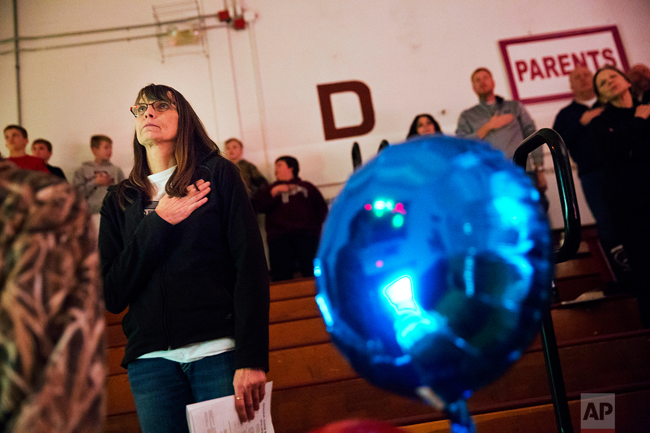 """Marlene Kramer stands for the national anthem while watching her stepdaughter cheerlead at a high school wrestling meet in Prairie du Chien, Wis., Thursday, Jan. 19, 2017. Kramer, who voted twice for Obama, used to watch Trump on """"Celebrity Apprentice."""" """"I said to myself, ugh, I can't stand him."""" And when he announced his candidacy, she thought it was a joke. """"Then my husband said to me, 'Just think, everything he touches seems to turn to money,'"""" she said, and she changed her mind. """"I'm hoping he'll make this country really rich."""" (AP Photo/David Goldman)"""