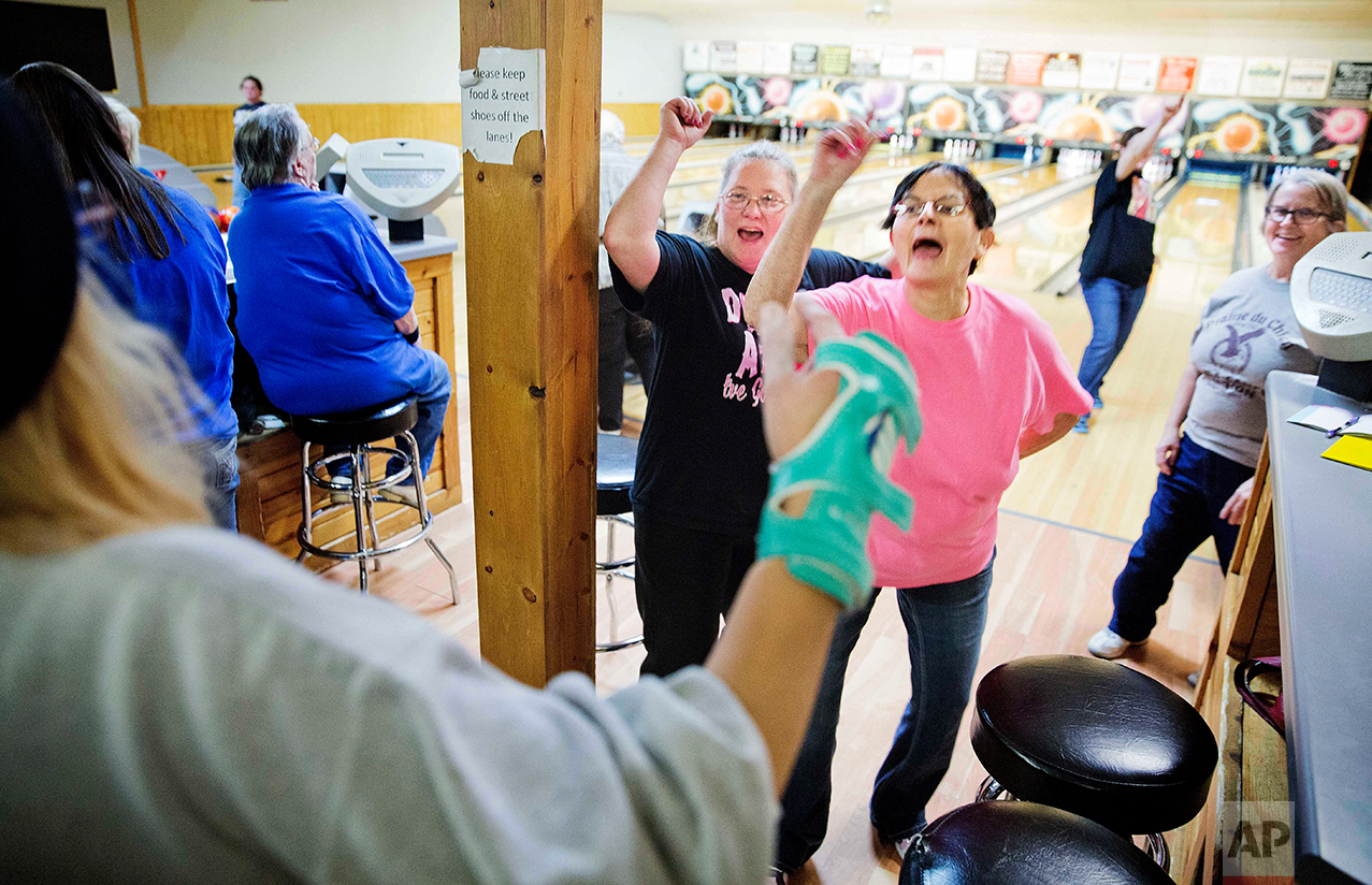 Jackie Suelflow, right, and Mikey Clanton, left, dance and sing during a ladies bowling night in Prairie du Chien, Wis., Wednesday, Jan. 18, 2017. Here in Crawford County, residents often recite two facts about their hometown, the first one proudly: It is the second-oldest community in the state. The next is that it's also one of the poorest. There are no rusted-out manufacturing plants to embody this discontent. The downtown main street bustles with tourists come summer. Just a few vacant storefronts hint at the seething resentment that life still seems harder here than it should. (AP Photo/David Goldman)