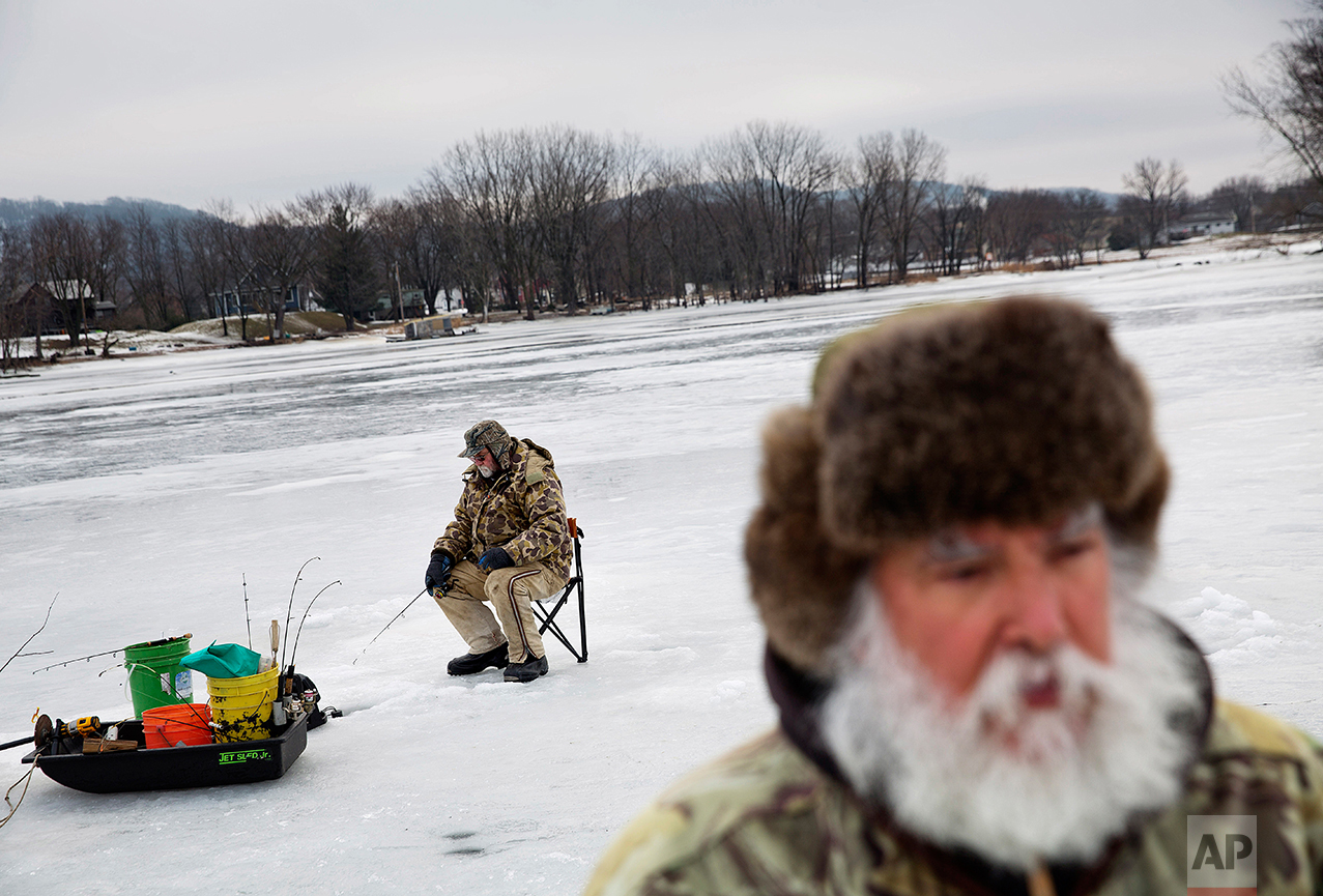 Mark Kleinow, background, ice fishes with his friend Rick Trudo, foreground, on a frozen portion of the Mississippi River in Prairie du Chien, Wis., Wednesday, Jan. 18, 2017. Trudo voted for Trump and Kleinow voted for Clinton. But the left-right, blue-red vitriol that has cleaved apart the country has not left the same scars here. (AP Photo/David Goldman)