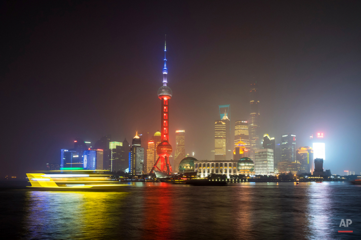 A ferry travels past the Oriental Pearl Tower, lit in the colors of the French flag in Shanghai, China, Saturday, Nov. 14, 2015, following the attacks in Paris on Friday.  Multiple attacks across Paris on Friday night have left scores dead and hundreds injured.. (Chinatopix Via AP) CHINA OUT