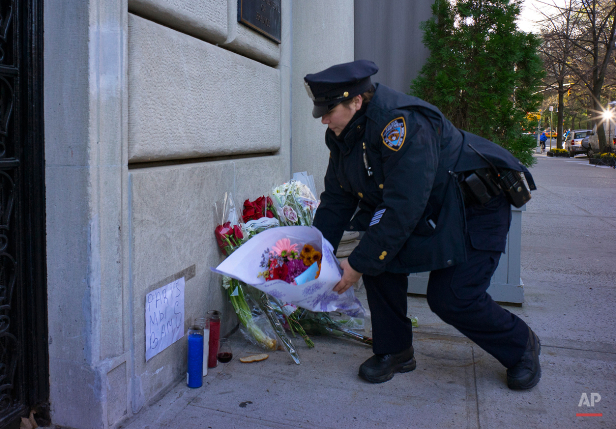 A New York City police officer adjusts wind blown flowers left as a sign of support to France near the door of the French consulate in New York, Saturday, Nov. 14, 2015.  Multiple attacks across Paris on Friday night have left scores dead and hundreds injured.(AP Photo/Craig Ruttle)