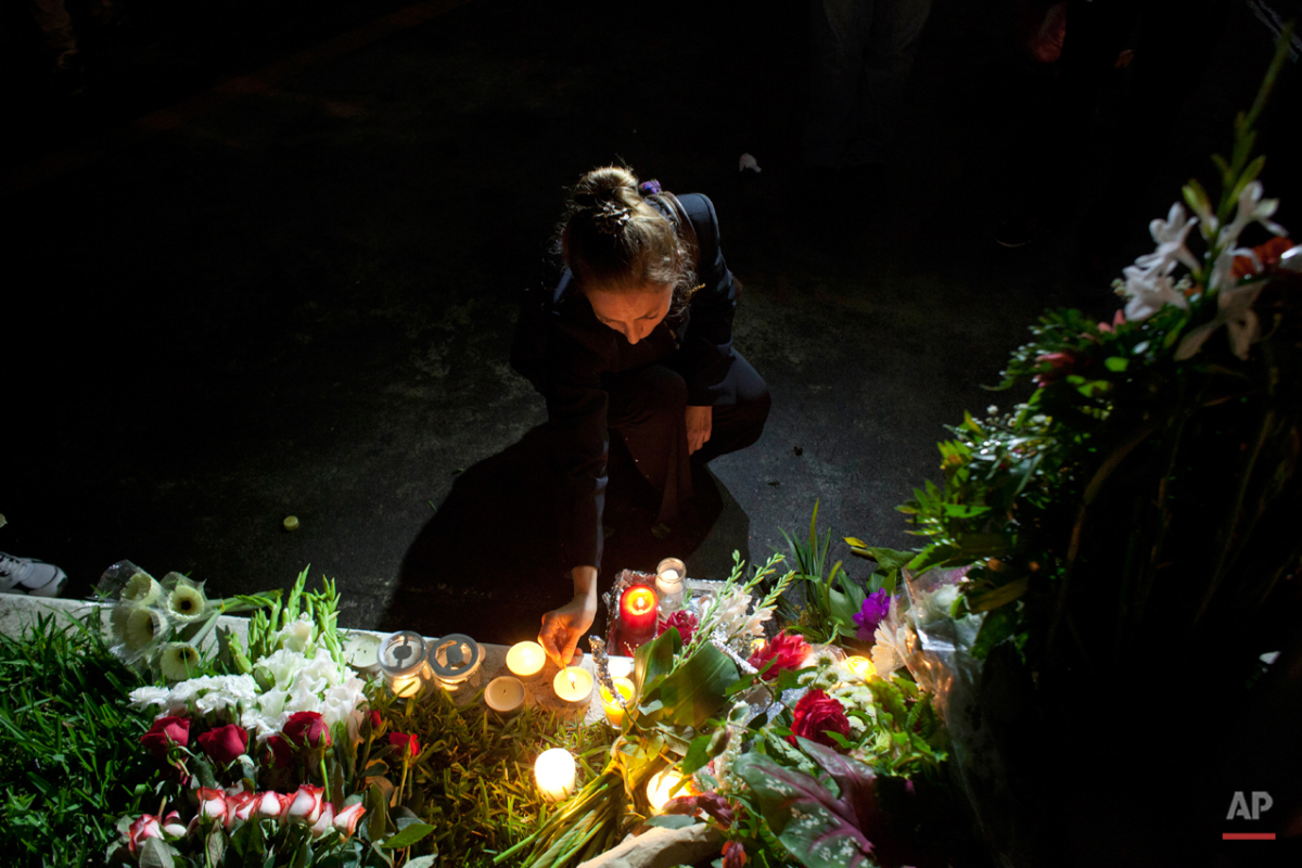 A woman lights a candle at the French embassy in Guatemala City, during a ceremony Sunday, Nov. 15, 2015, in homage to the victims of the deadly attacks in Paris. Multiple terrorist attacks across Paris on Friday night left more than one hundred dead and many more injured. (AP Photo/Moises Castillo)