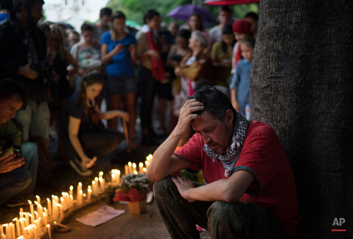 A man sits next to the candles during a homage to the victims of the deadly attacks in Paris, at a square in Rio de Janeiro, Brazil, Sunday, Nov. 15, 2015. Multiple terrorist attacks across Paris on Friday night left more than one hundred dead and many more injured. (AP Photo/Leo Correa)