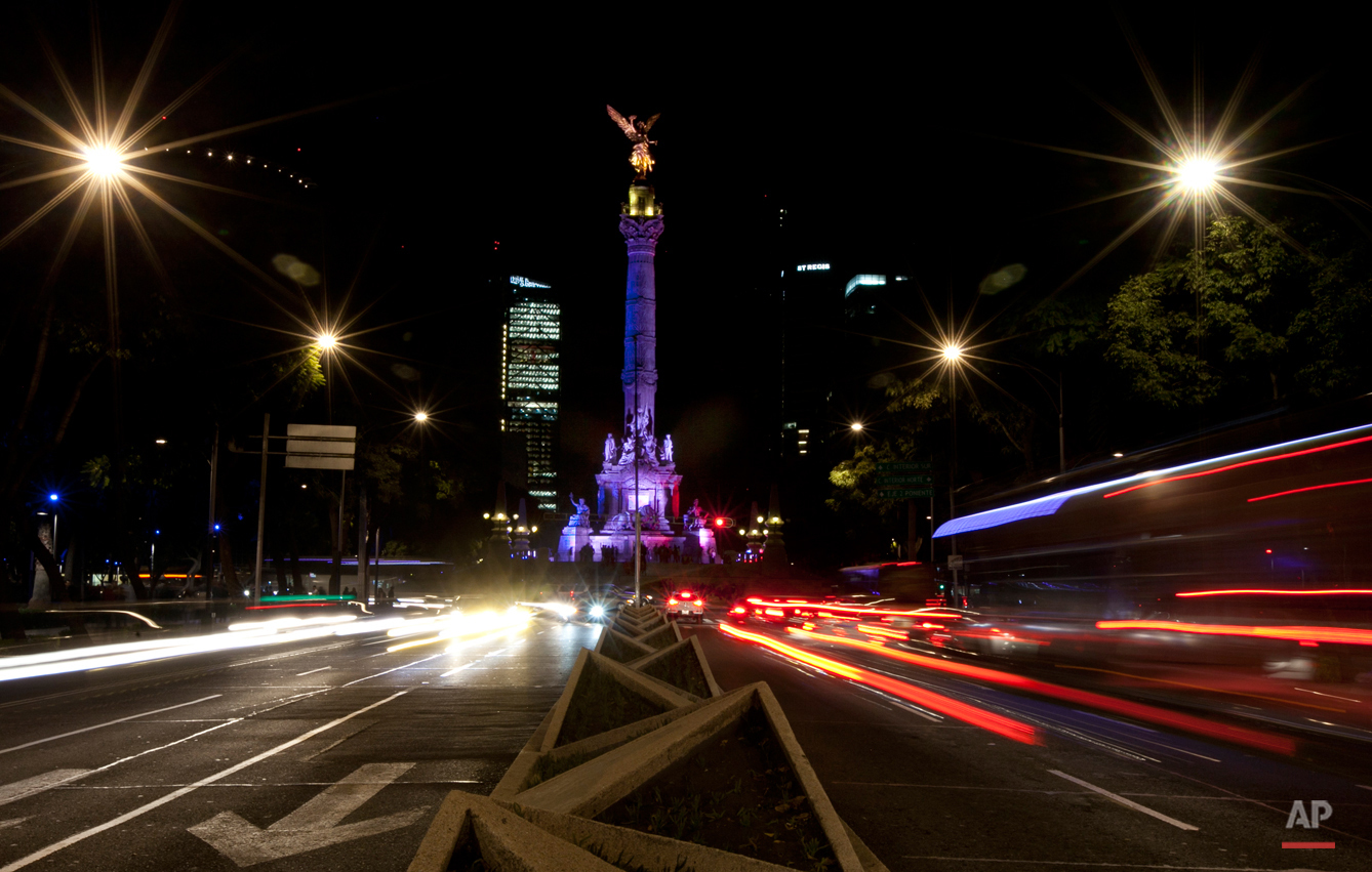 The iconic Angel of Independence monument is lit in the colors of the French flag in Mexico City, Saturday, Nov. 14, 2015,  in memory of the victims of attacks in Paris. French President Francois Hollande said Saturday at least 127 people died Friday night when attackers launched gun attacks at Paris cafes, detonated suicide bombs near France's national stadium and killed hostages inside a concert hall during a rock show. More than 200 people were hurt, dozens critically. (AP Photo/Marco Ugarte)