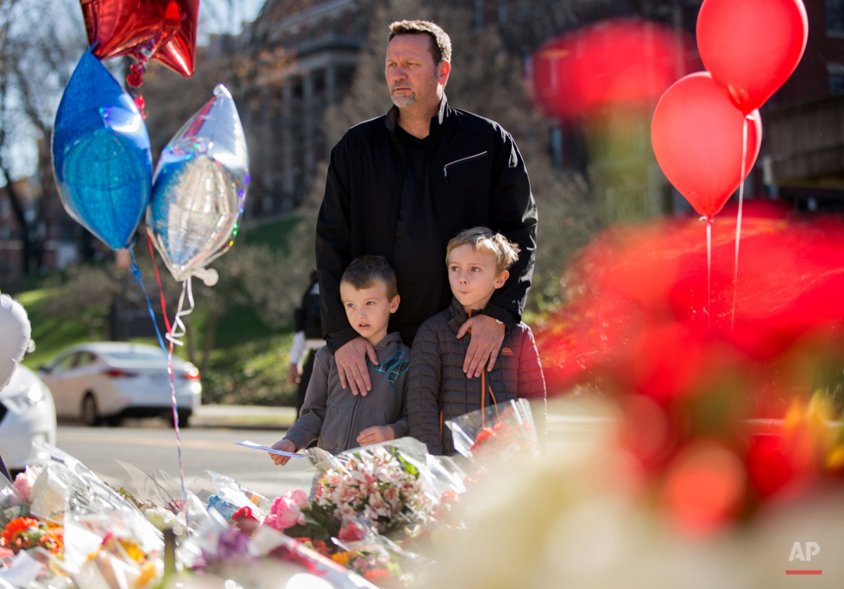 James Jones of Woodbridge, Va., brings his two sons Riley, 7, and Grayson, 5, to a memorial outside the gates of the French Embassy in Washington, Sunday, Nov. 15, 2015. The Islamic State group claimed responsibility for Friday's attacks on a stadium, a concert hall and Paris cafes that left more than 120 people dead and over 350 wounded.  (AP Photo/Andrew Harnik)