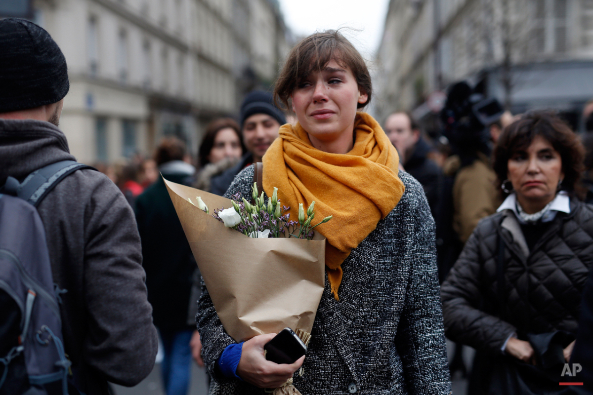 A woman carrying flowers cries in front of the Carillon cafe and the Petit Cambodge restaurant in Paris Saturday Nov. 14, 2015, a day after  a series of attacks in Paris.  French officials  said scores of people died Friday night when attackers launched gun attacks at Paris cafes, detonated suicide bombs near France's national stadium and killed hostages inside a concert hall during a rock show.   (AP Photo/Jerome Delay)