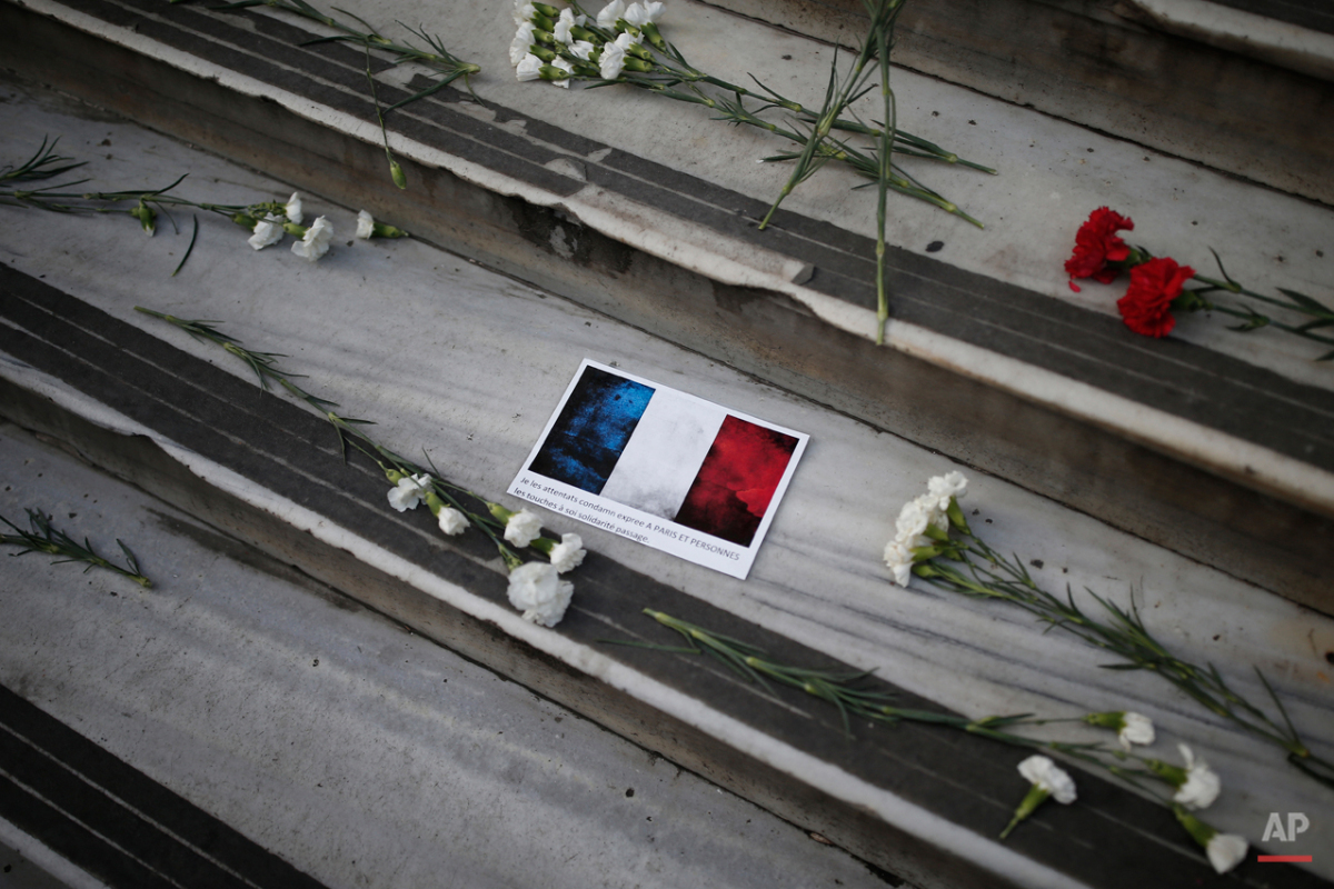Carnations and messages are left by people outside the French consulate in Istanbul, Turkey, Saturday, Nov. 14, 2015, after the attacks in Paris on Friday. French President Francois Hollande vowed to attack the Islamic State group without mercy as the jihadist group admitted responsibility Saturday for orchestrating the deadliest attacks inflicted on France since World War II. (AP Photo/Emrah Gurel)