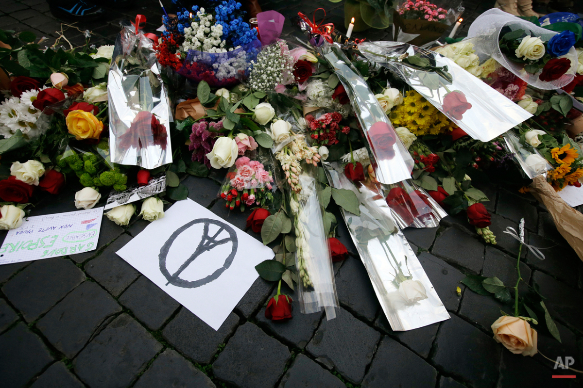 Flowers are laid outside the French embassy in Rome, Saturday, Nov. 14, 2015. French police on Saturday hunted possible accomplices of eight assailants who terrorized Paris concert-goers, cafe diners and soccer fans with a coordinated string of suicide bombings and shootings in France's deadliest peacetime attacks. (AP Photo/Gregorio Borgia)