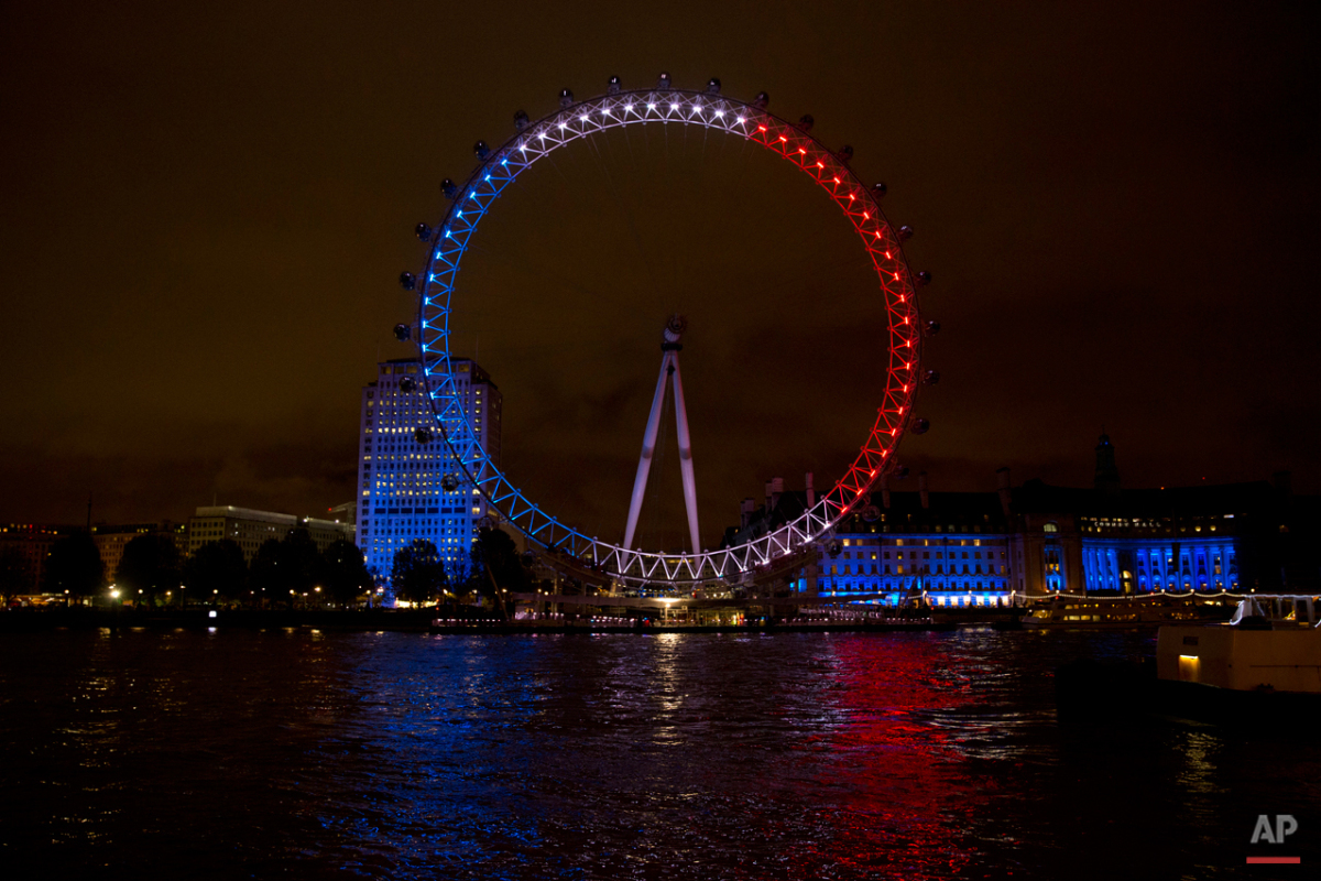 The London Eye ferris wheel is lit up in the colors of the French flag in solidarity with France after the deadly attacks in Paris, in London, Saturday, Nov. 14, 2015.  Multiple attacks across Paris on Friday night have left scores dead and hundreds injured. (AP Photo/Matt Dunham)