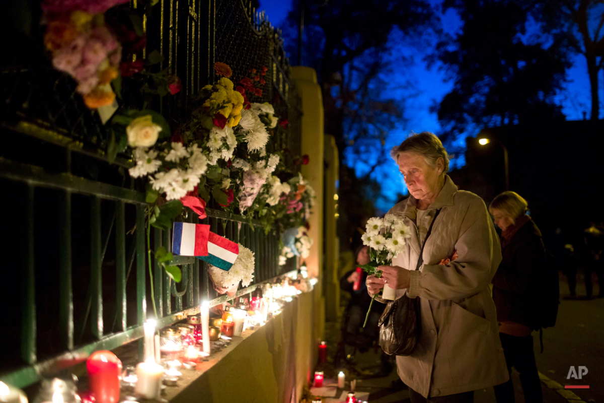 A woman lays flowers to pay tribute to the victims of  Paris Attacks outside the French Embassy in Budapest, Hungary, Saturday, Nov. 14, 2015.  Multiple attacks across Paris on Friday night have left scores dead and hundreds injured. (Balazs Mohai/MTI via AP)