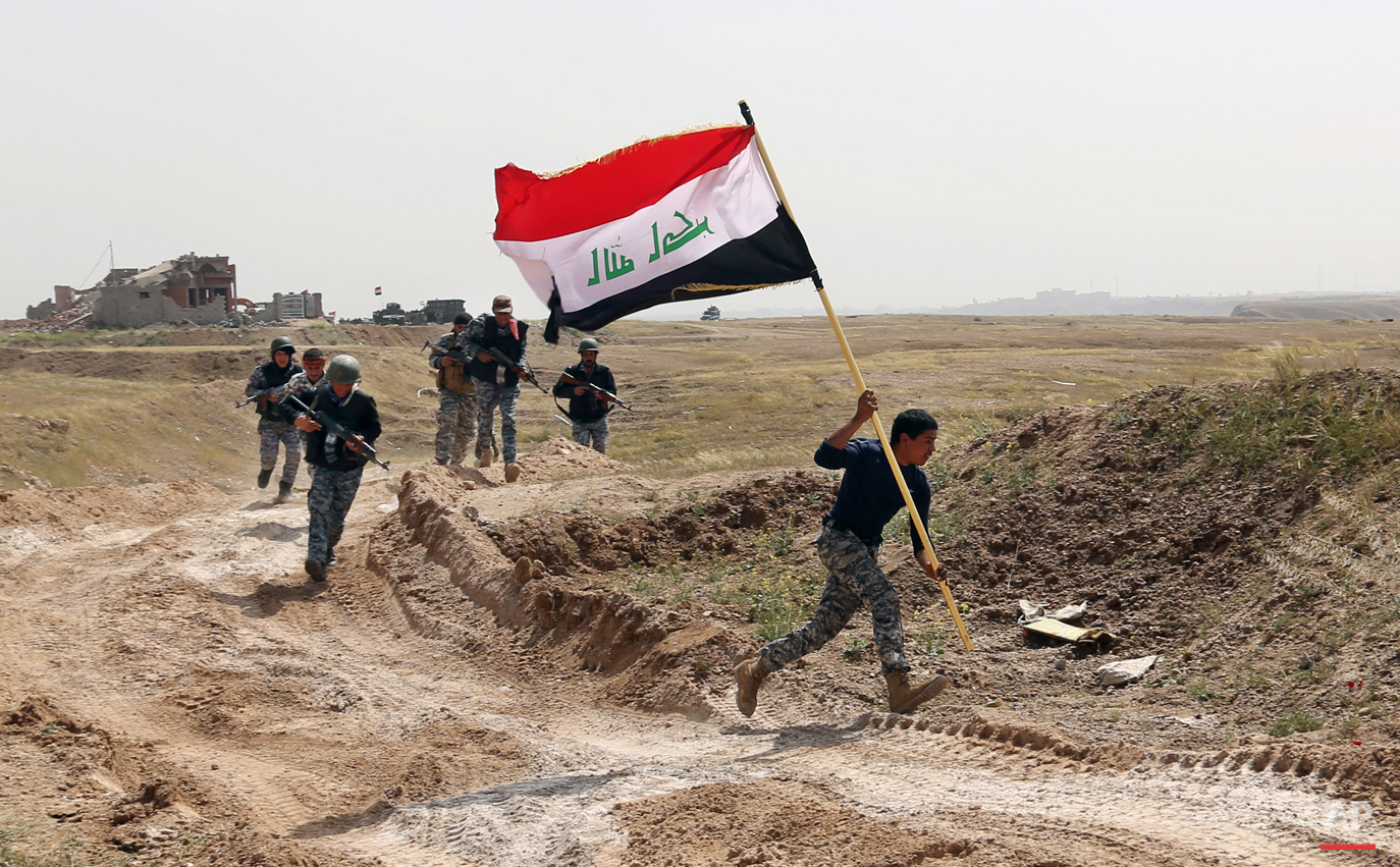 A member of the Iraqi security forces runs to plant the national flag as they surround Tikrit during clashes to regain the city from Islamic State militants, 80 miles (130 kilometers) north of Baghdad, Iraq, Monday, March 30, 2015. (AP Photo/Khalid Mohammed)