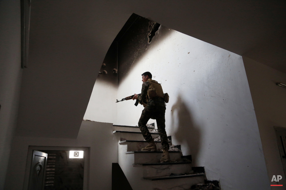 An Iraqi soldier searches a for fighters of Islamic State group in Tikrit, 80 miles (130 kilometers) north of Baghdad, Iraq, Monday, March 30, 2015. (AP Photo/Khalid Mohammed)