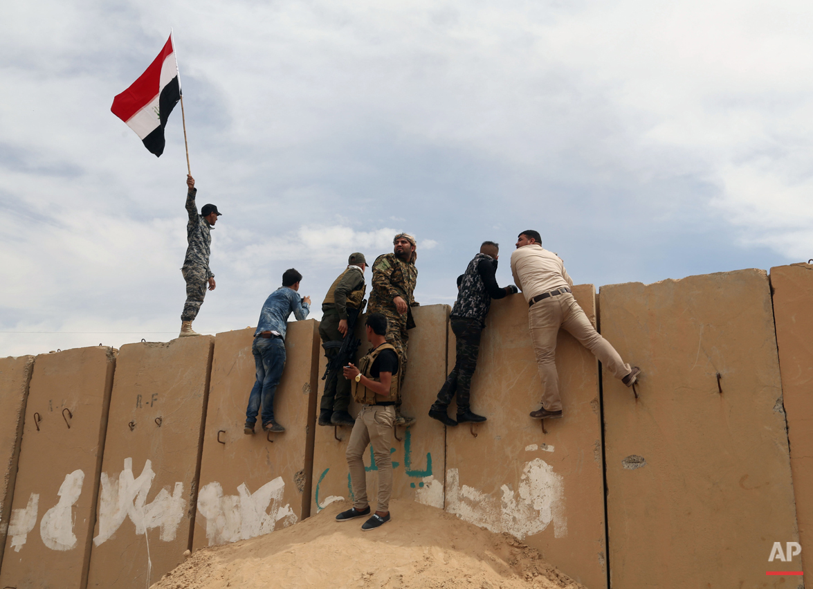 Iraqi security forces watch movements of their enemy at the front line, during clashes between Iraqi security forces and Islamic State group extremists in Tikrit, 130 kilometers (80 miles) north of Baghdad, Iraq, Saturday, March 28, 2015.  (AP Photo/Khalid Mohammed)