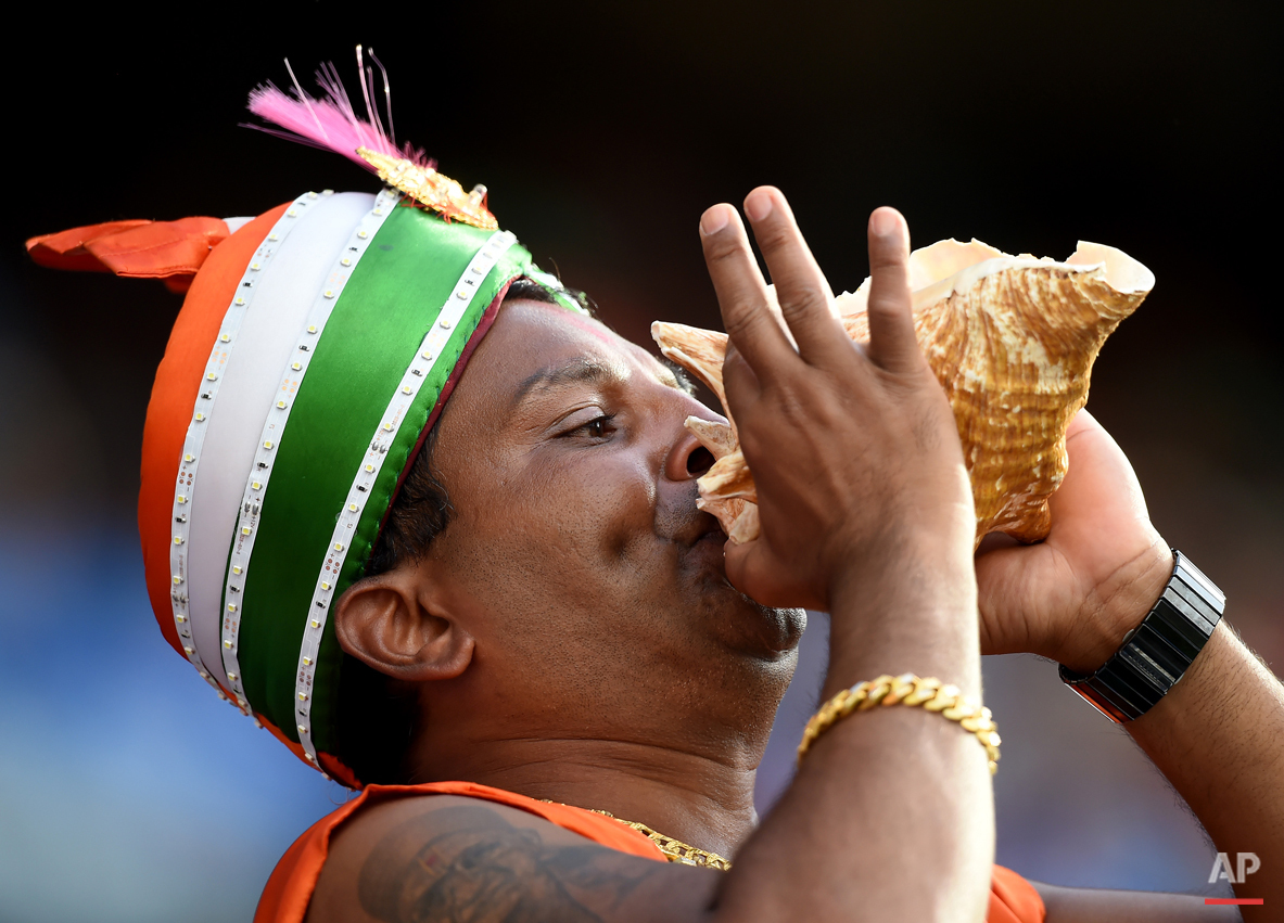 A Indian supporter blows on a shell as he supports his team during their Cricket World Cup quarterfinal match against Bangladesh in Melbourne, Australia, Thursday, March 19, 2015. (AP Photo/Andy Brownbill)