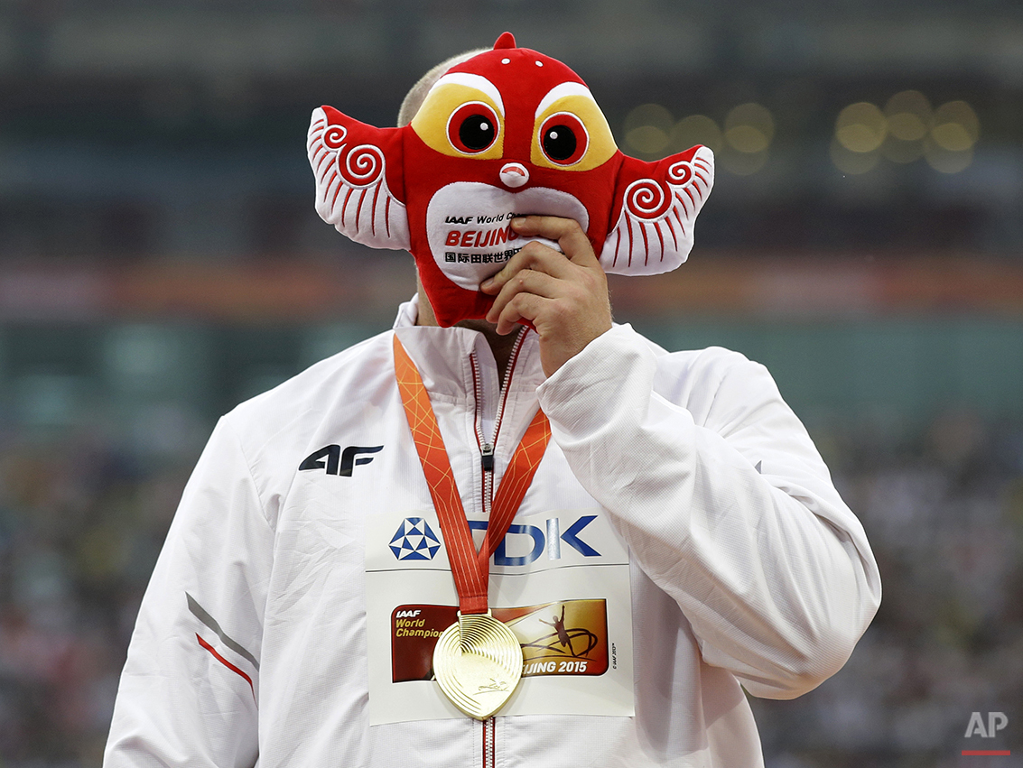 Men's discus gold medalist Poland's Piotr Malachowski celebrates on the podium at the World Athletics Championships at the Bird's Nest stadium in Beijing, Sunday, Aug. 30, 2015. (AP Photo/Kin Cheung)