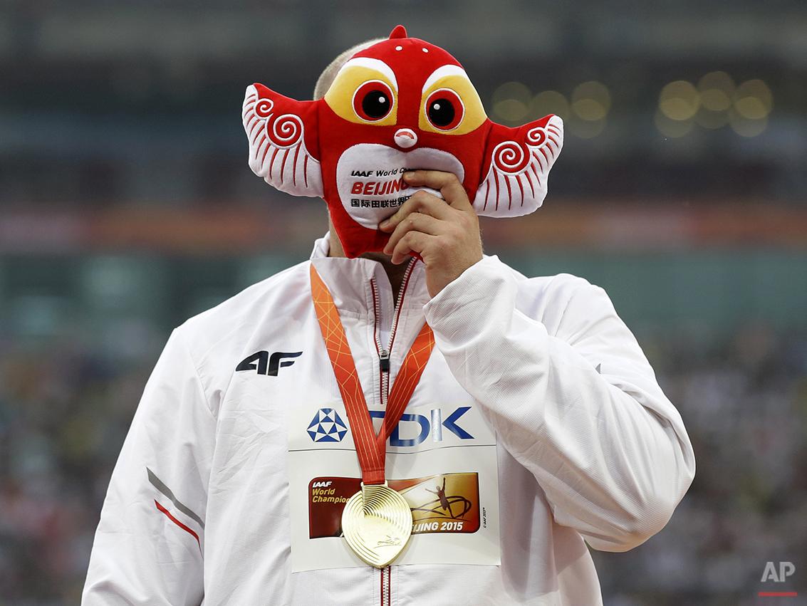Men's discus gold medalist Poland's Piotr Malachowski celebrates on the podium at the World Athletics Championships at the Bird's Nest stadium in Beijing, Sunday, Aug. 30, 2015. (AP Photo/Kin Cheung)