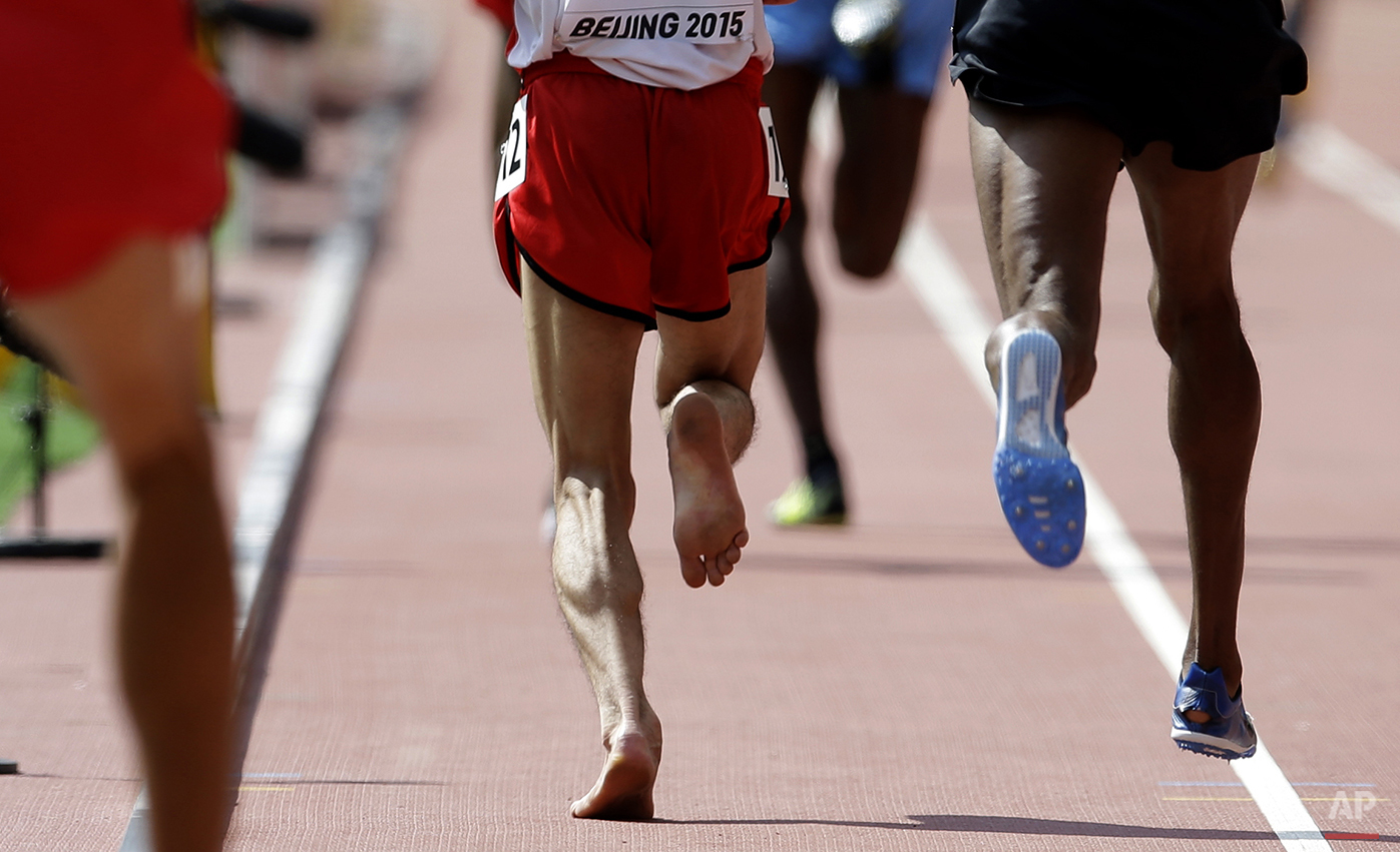 Yemen's Abdullah Al-Qwabani competes barefoot in a men's 5000m round one heat at the World Athletics Championships at the Bird's Nest stadium in Beijing, Wednesday, Aug. 26, 2015. (AP Photo/Kin Cheung)