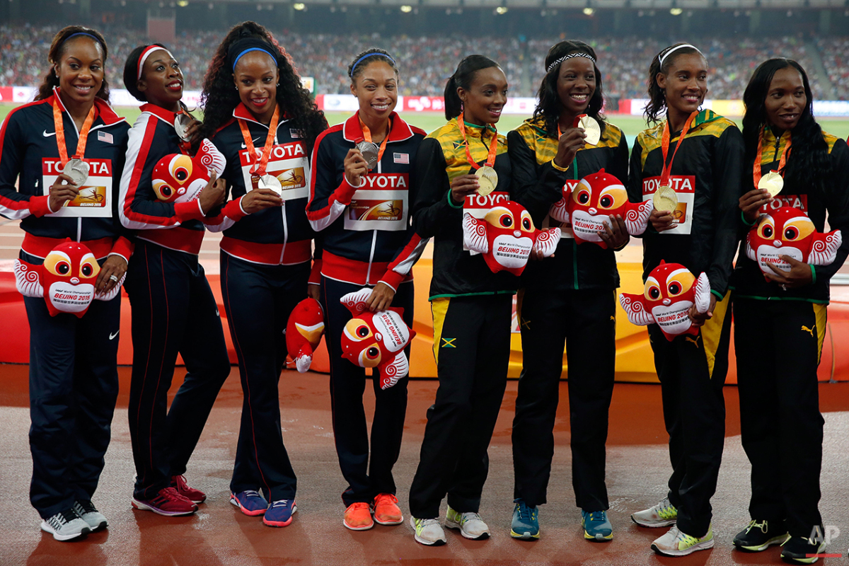 The teams of the United States, silver, left, and Jamaica, gold, pose with their medals during the ceremony for the women's 4x400m relay  at the World Athletics Championships at the Bird's Nest stadium in Beijing, Sunday, Aug. 30, 2015. (AP Photo/Ng Han Guan)