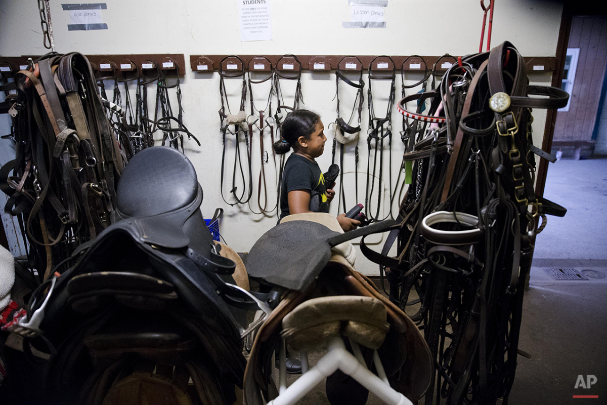 In this July 29, 2015, photo, Work to Ride participant Marisol Jimenez, 9, gathers equipment from the tack room ahead of a ride on the pony Lyric in Philadelphia. Marisol's mother decided to get Marisol involved in Work to Ride, a non-profit program at the Chamounix Equestrian Center in Philadelphia's Fairmount Park. (AP Photo/Matt Rourke)