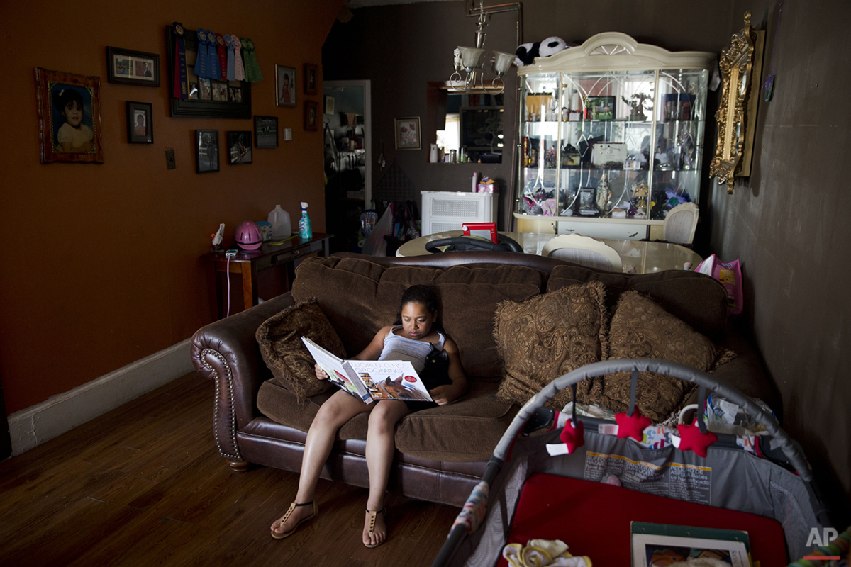 In this July 16, 2015 photo, Marisol Jimenez reads a book about horses at her home in Philadelphia. Marisol's mother decided to get Marisol involved in Work to Ride, a non-profit program. Marisol and 19 other kids in Work to Ride muck down stalls, brush horses, shovel out hay and droppings, and keep the stables clean and running. In exchange, they receive horseback riding lessons, and a chance to be on their nationally recognized polo team. (AP Photo/Matt Rourke)