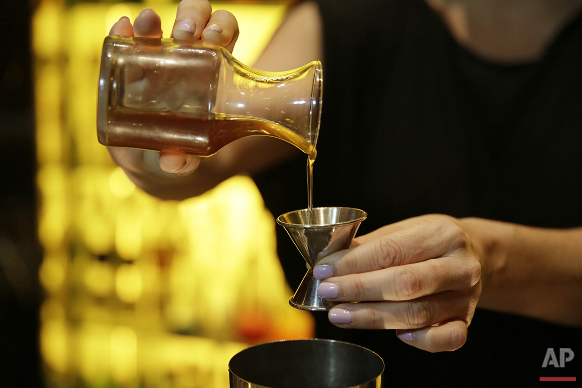 In this photo taken Monday, April 18, 2016, honey is used as an ingredient to make a 49er Tea Time cocktail in the Redwood Room at the Clift Hotel in San Francisco.(AP Photo/Eric Risberg)