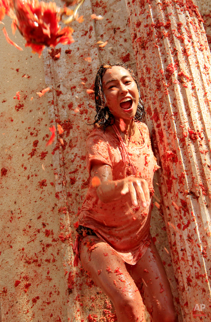 """A woman throws a tomato during the annual """"tomatina"""" tomato fight fiesta, in the village of Bunol, 50 kilometers outside Valencia, Spain, Wednesday, Aug. 26, 2015. The streets of an eastern Spanish town are awash with red pulp as thousands of people pelt each other with tomatoes in the annual """"Tomatina"""" battle that has become a major tourist attraction. At the annual fiesta in Bunol on Wednesday, trucks dumped 150 tons of ripe tomatoes for some 22,000 participants, many from abroad to throw during the hour-long morning festivities. (AP Photo/Alberto Saiz)"""