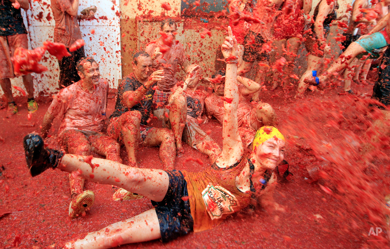 """People sit and lie on the ground during the annual """"tomatina"""" tomato fight fiesta, in the village of Bunol, 50 kilometers outside Valencia, Spain, Wednesday, Aug. 26, 2015. The streets of an eastern Spanish town are awash with red pulp as thousands of people pelt each other with tomatoes in the annual """"Tomatina"""" battle that has become a major tourist attraction. At the annual fiesta in Bunol on Wednesday, trucks dumped 150 tons of ripe tomatoes for some 22,000 participants, many from abroad to throw during the hour-long morning festivities. (AP Photo/Alberto Saiz)"""