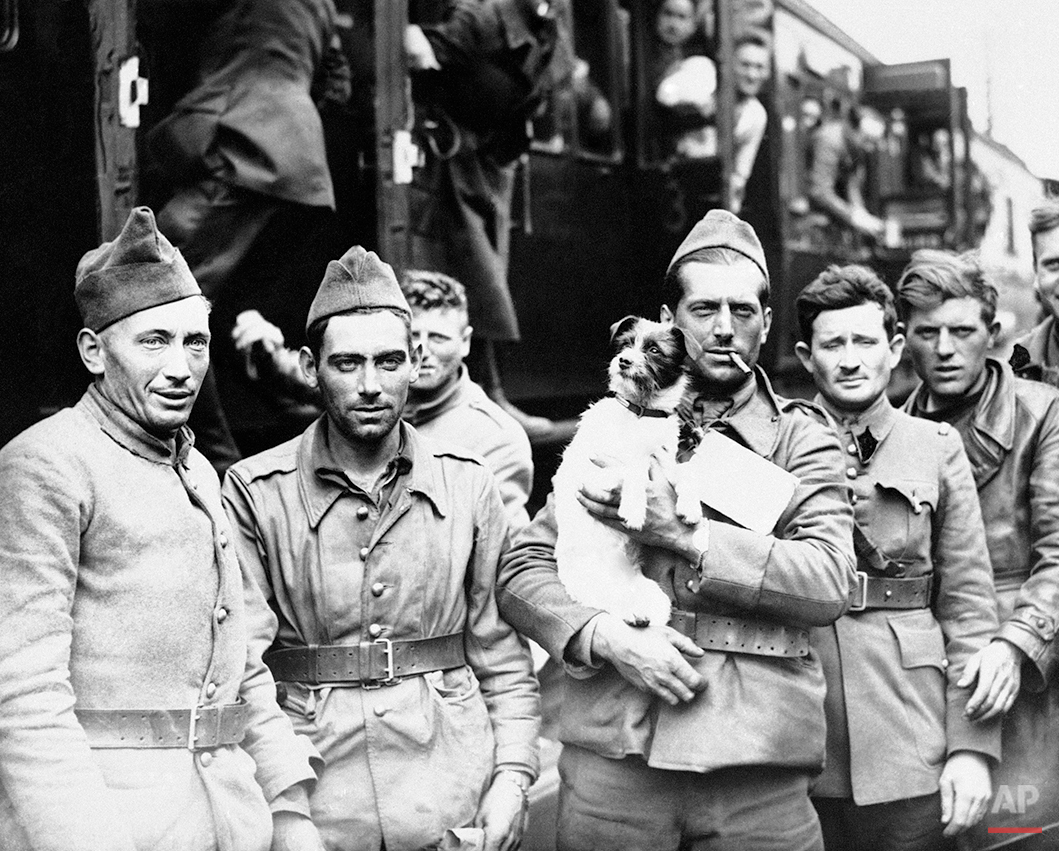 Tons of thousands of more troops have poured into England during the night, after heroically fighting their way out of Northern France and Belgium. French troops with the dog they rescued, seen during a halt at a wayside station on June 24, 1940. A large number of dogs have been brought over by the gallant Allied soldiers. (AP Photo)